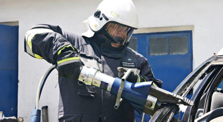 Strażak z OSP Gostyń ćwiczy cięcie słupka A narzędziem marki Lucas