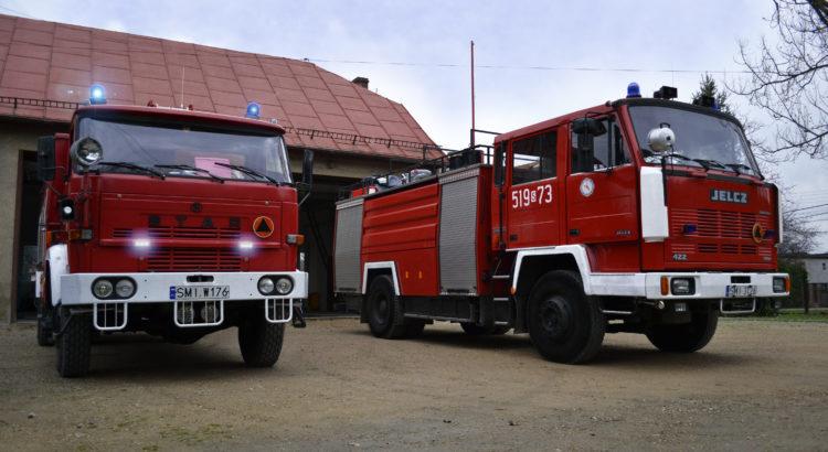 Dwa wozy pożarnicze stoją na placu przed remizą
