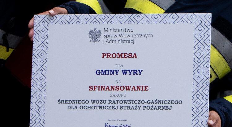 Wielkoformatowa karta z napisem: promesa dla Gminy Wyry podpisana przez Mariusza Kamińskiego.