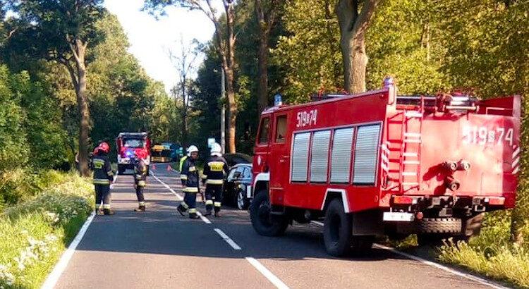 Samochód pożarniczy na prawym skraju drogi osłania miejsce wypadku.
